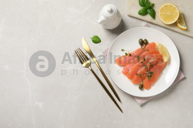 Delicious salmon carpaccio served on light grey table, flat lay. Space for text