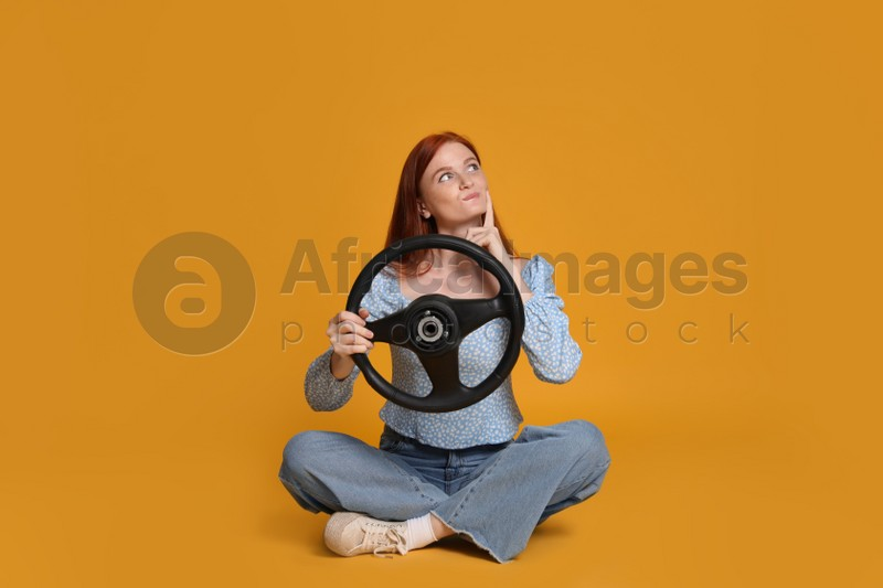 Young woman with steering wheel on yellow background