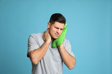 Man using hot water bottle to relieve neck pain on light blue background