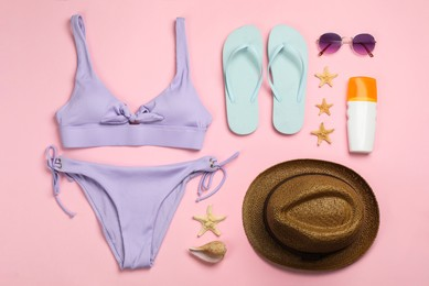 Flat lay composition with beach objects on pink background