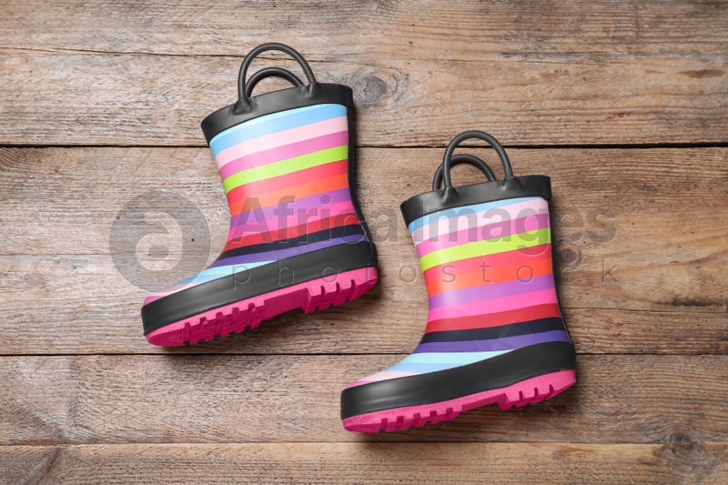 Pair of striped rubber boots on wooden background, top view