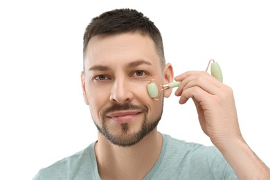 Man using nephrite facial roller on white background