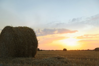 Beautiful view of agricultural field with hay bale at sunset