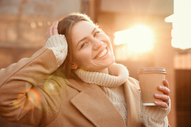 Young woman with cup of coffee on city street in morning