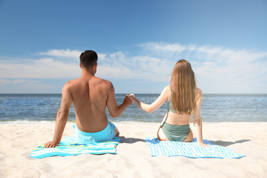 Woman in bikini and her boyfriend sunbathing on beach, back view. Lovely couple