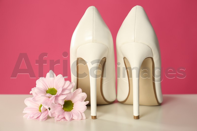 Beautiful tender flowers and woman's shoes on white table