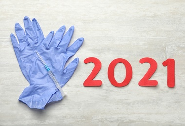 Number 2021, syringe with coronavirus vaccine and medical gloves on white background, flat lay