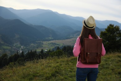 Woman enjoying mountain landscape, back view. Space for text