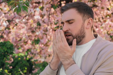 Man suffering from seasonal pollen allergy near blossoming tree outdoors