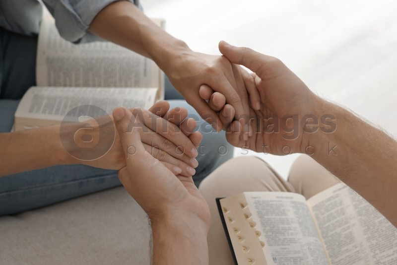 Religious people with Bibles holding hands and praying together indoors, closeup