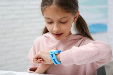 Girl with stylish smart watch at table indoors