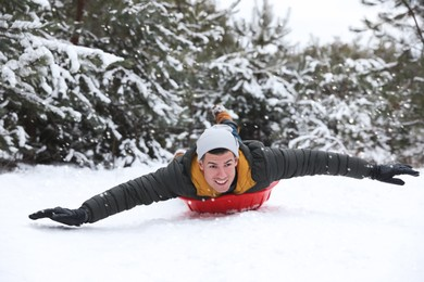 Happy man sledding outdoors on winter day. Christmas vacation