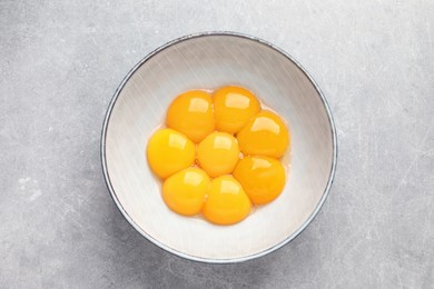 Bowl with raw egg yolks on grey table, top view