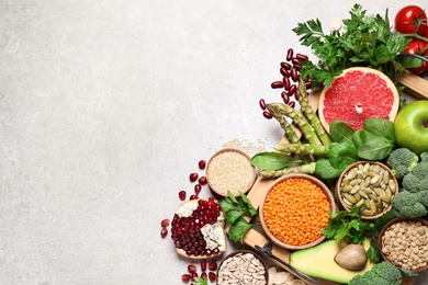 Fresh vegetables, fruits and seeds on grey table, flat lay. Space for text