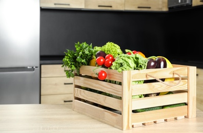 Wooden crate with vegetables on table in kitchen. Space for text