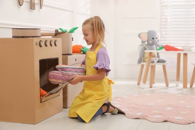 Little girl playing with toy cardboard oven at home