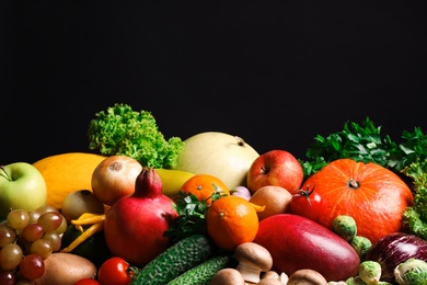 Assortment of fresh organic fruits and vegetables on black background
