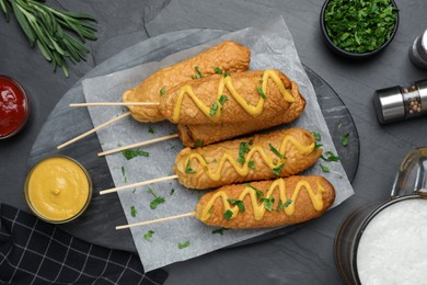 Delicious deep fried corn dogs and sauces on black table, flat lay
