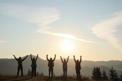 Group of people enjoying sunrise in mountains, back view. Space for text