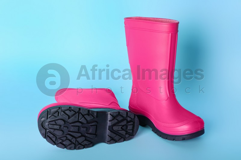 Pair of bright pink rubber boots on light blue background