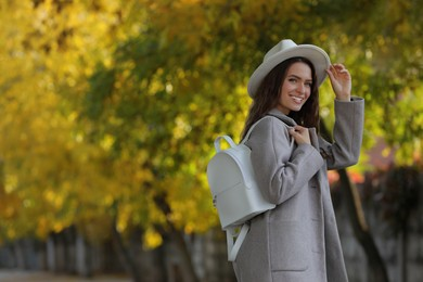 Young woman with stylish white backpack on city street, space for text