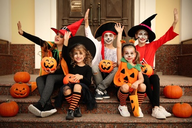 Cute little kids with pumpkins wearing Halloween costumes on stairs outdoors