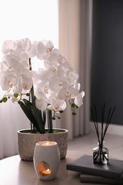 Beautiful orchid, burning candles and air reed freshener on table indoors