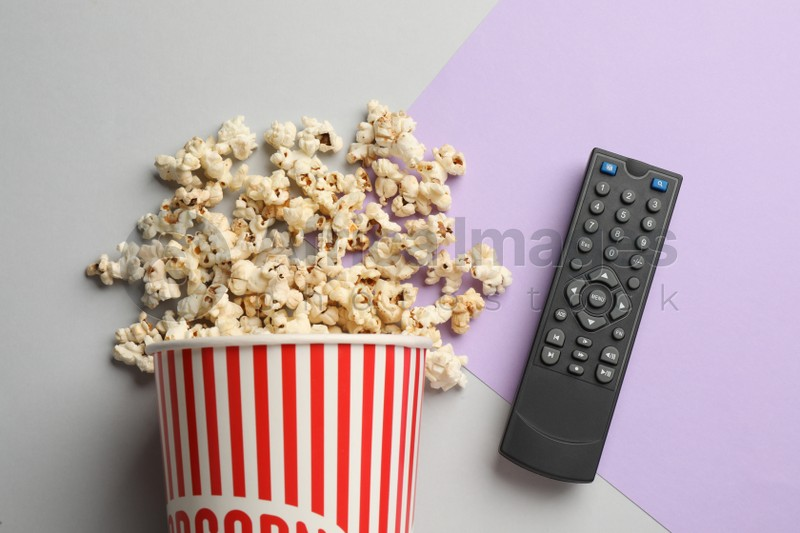 Modern tv remote control and popcorn on color background, flat lay