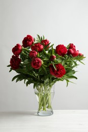 Beautiful bouquet of red peony flowers in glass vase on white table