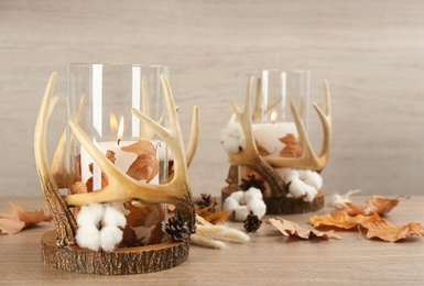 Burning candles in beautiful glass holders, cotton flowers and autumn leaves on wooden table