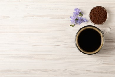 Glass cup of delicious chicory drink, granules and flowers on white wooden table, flat lay. Space for text