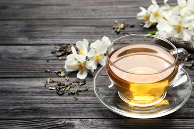 Glass cup of aromatic jasmine tea and fresh flowers on black wooden table, space for text