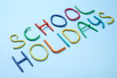 Phrase School Holidays made of modeling clay on light blue background
