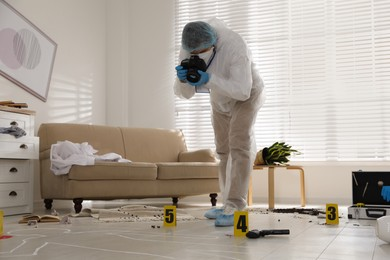Investigator in protective suit making photo of crime scene indoors
