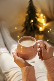 Woman holding cup with hot drink near festive lights at home, closeup