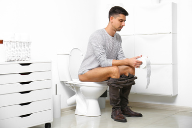 Man with paper roll sitting on toilet bowl in bathroom