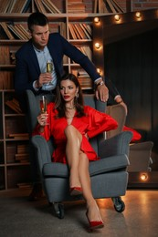 Beautiful couple with glasses of champagne indoors. Luxury lifestyle