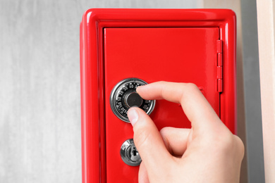Man opening steel safe with mechanical combination lock, closeup