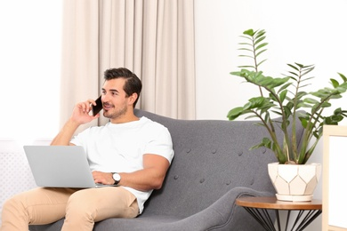Handsome young man talking on phone while working with laptop indoors