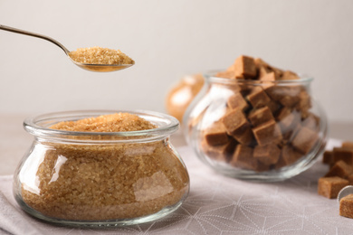 Taking spoon of brown sugar from glass bowl on table