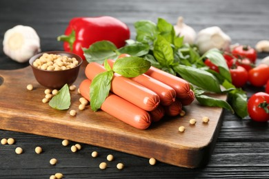 Fresh raw vegetarian sausages with basil, soybeans and vegetables on black wooden table
