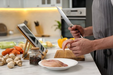 Man making dinner while watching online cooking course via tablet in kitchen, closeup