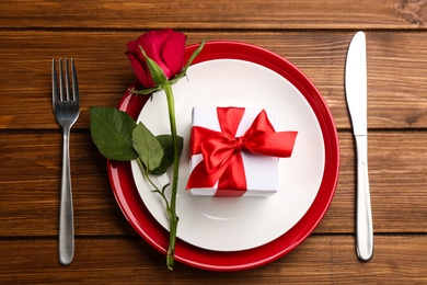 Beautiful table setting for Valentine's Day dinner on wooden background, flat lay