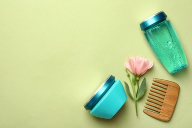Hair care cosmetic products, wooden comb and flower on light green background, flat lay. Space for text