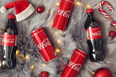 MYKOLAIV, UKRAINE - January 01, 2021: Flat lay composition with Coca-Cola drinks and Christmas decorations on fur background