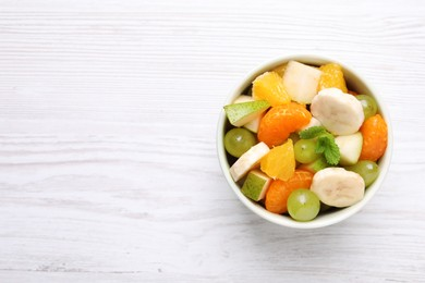 Delicious fresh fruit salad in bowl on white wooden table, top view. Space for text