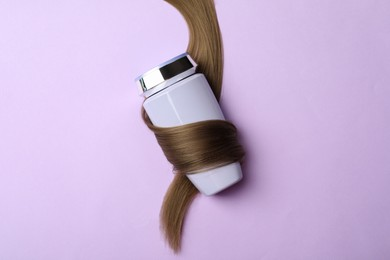 Bottle wrapped in lock of hair on violet background, top view. Natural cosmetic product