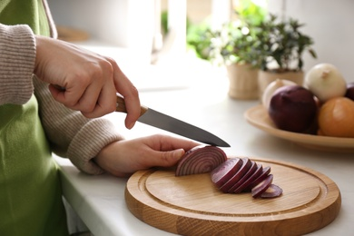 Woman cutting red onion into slices at countertop in kitchen, closeup