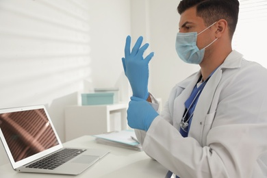 Doctor in protective mask putting on medical gloves at table in office