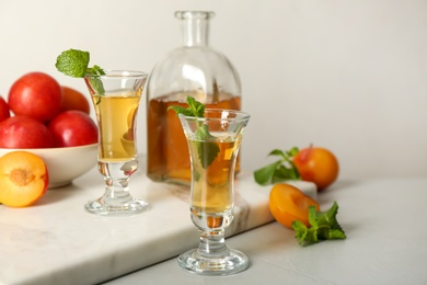 Delicious plum liquor with mint and ripe fruits on light table. Homemade strong alcoholic beverage